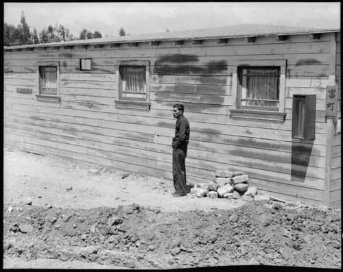 San Bruno, California. Many evacuees suffer from lack of their accustomed activity. The attitude of the man shown in this photograph is typical of the residents in assembly centers, and because there is not much to do and not enough work available, they mill around, they visit, they stroll and they linger to while away the hours.